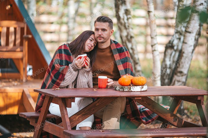 Young couple with coffe on yard of their house at autumn