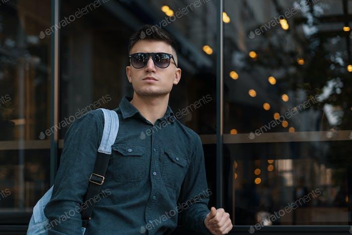 Современный молодой мужчина с солнцезащитных очками и рюкзаком
