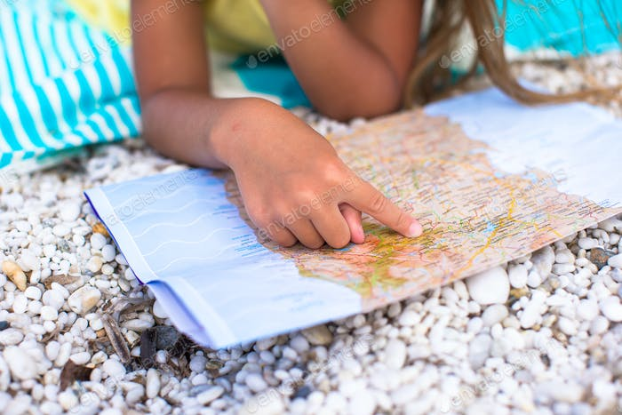 Adorable little girl with big map on tropical beach vacation