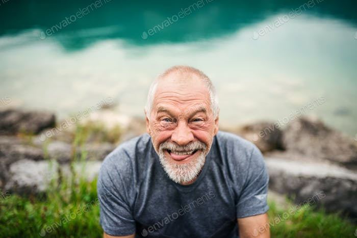 A portrait of senior man pensioner standing outdoors in nature, grimacing.