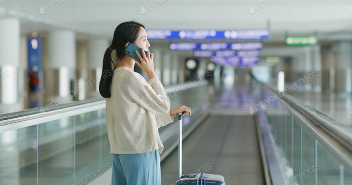 Woman have a call with her luggage at the airport