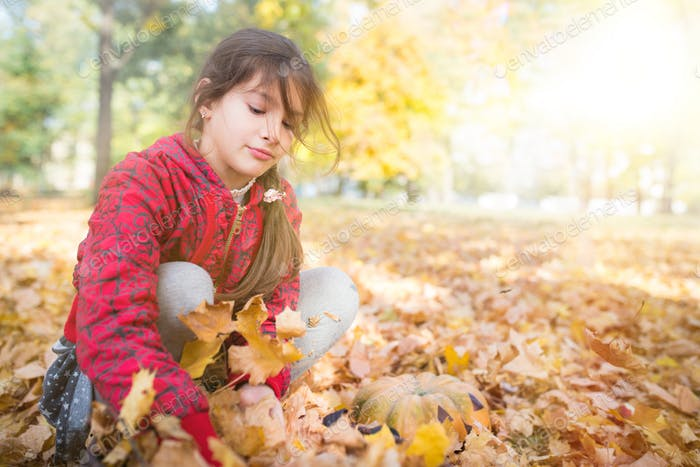 One little cute child play with yellow maple leaves