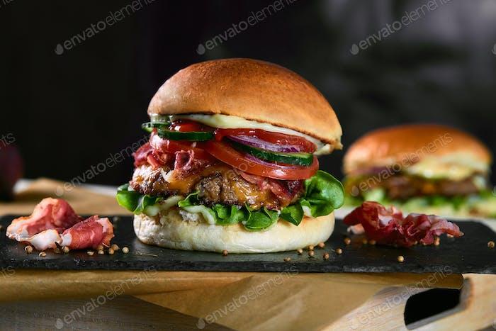 Big Sandwich - Hamburger with beef, beacon, tomato and Jalapeno sauce on dark background.