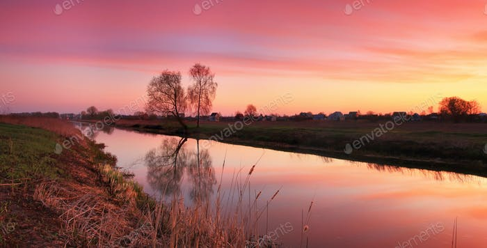 Beautiful sunset over the river in the spring countryside