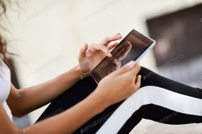 Young woman hands using digital tablet outdoors.