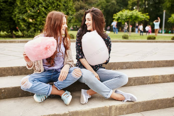Two sisters eating cotton candy at the park
