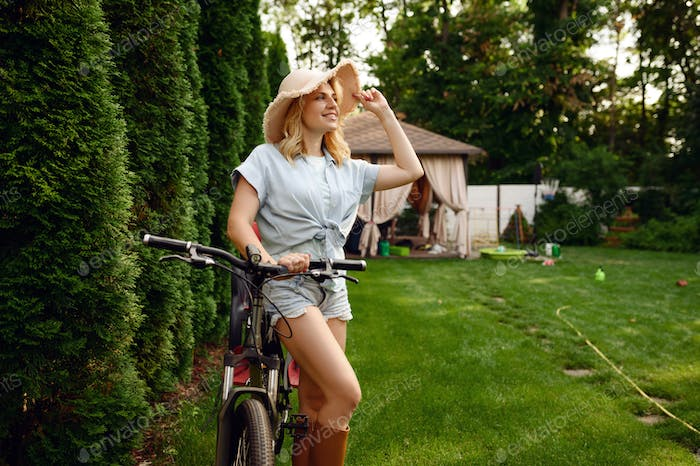 Female gardener poses on bicycle in the garden
