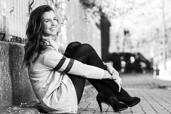 Funny female model of fashion with high heels sitting on the flo