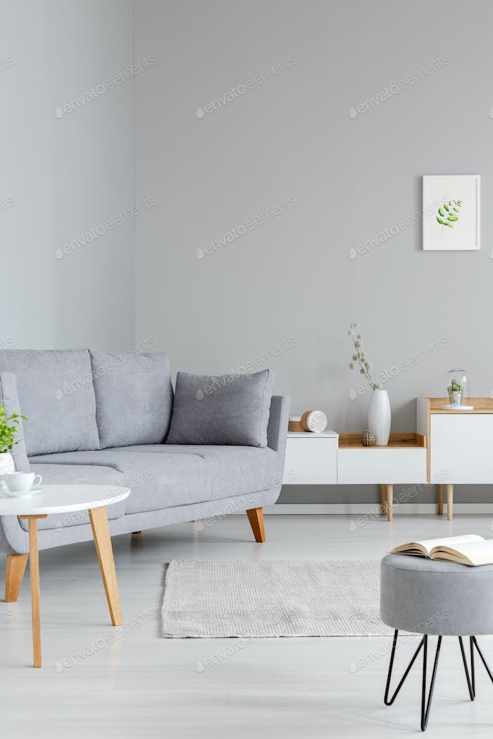 Simple, white and gray living room interior with a book on a sto