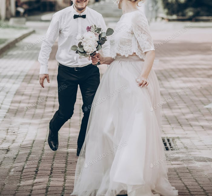 stylish wedding bride and groom having fun in sunny park
