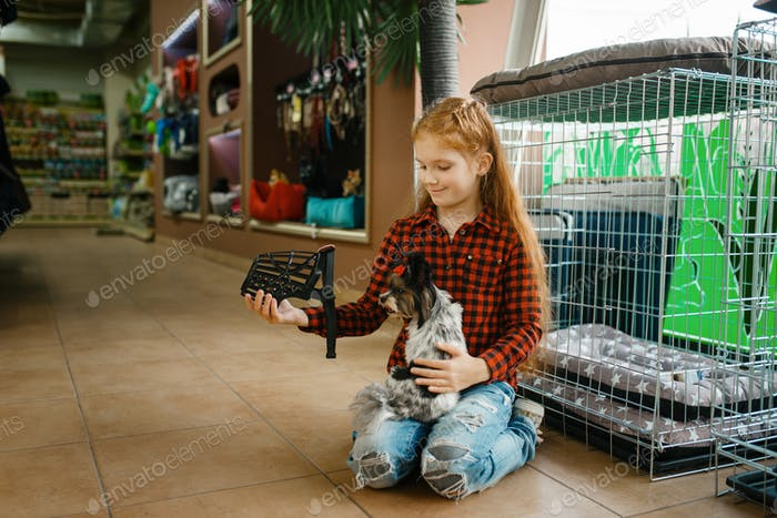 Little girl choosing muzzle for puppy, pet store