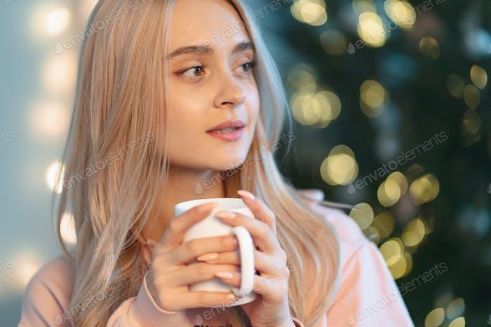 Eine hübsche junge Frau, die sich etwas wünscht, während sie eine heiße Tasse m trinkt