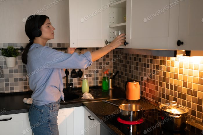 Woman putting dishware in cupboard in kitchen