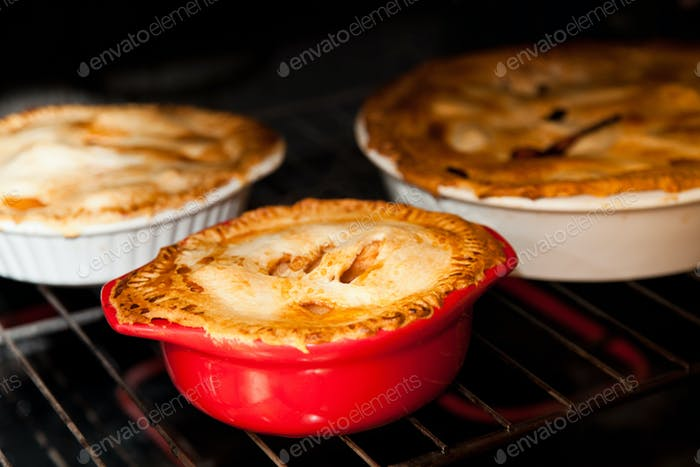 three apple pies cooking in the oven