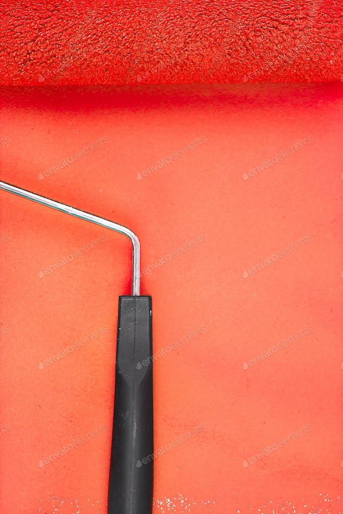 Rote Farbrolle mit Griff auf einem Hintergrund