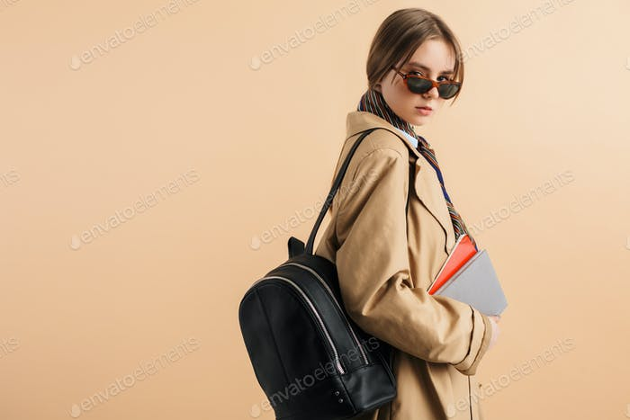 Young pretty girl in trench coat and sunglasses with backpack on shoulder holding notepads