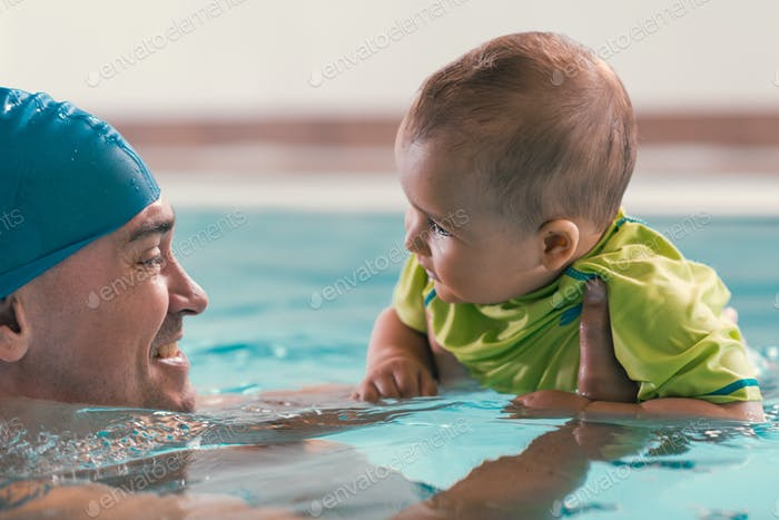 Father with baby boy in the swimming pool