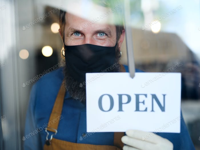 Coffee shop man owner with face mask, open after lockdown quarantine