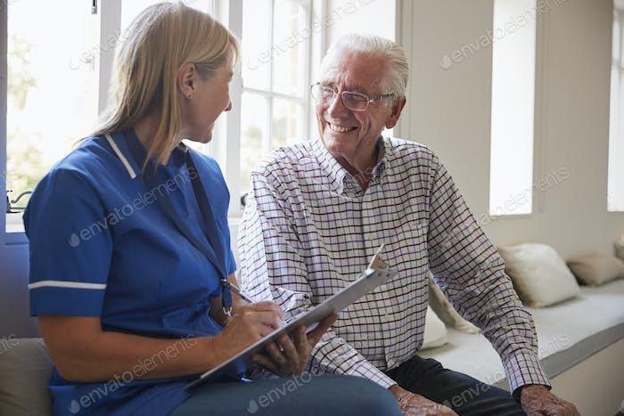 Senior man sits with nurse making notes at retirement home