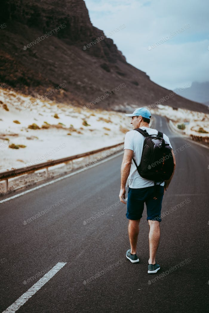 Traveler with backpack walks in the center of an epic winding road. Huge volcanic mountains in the