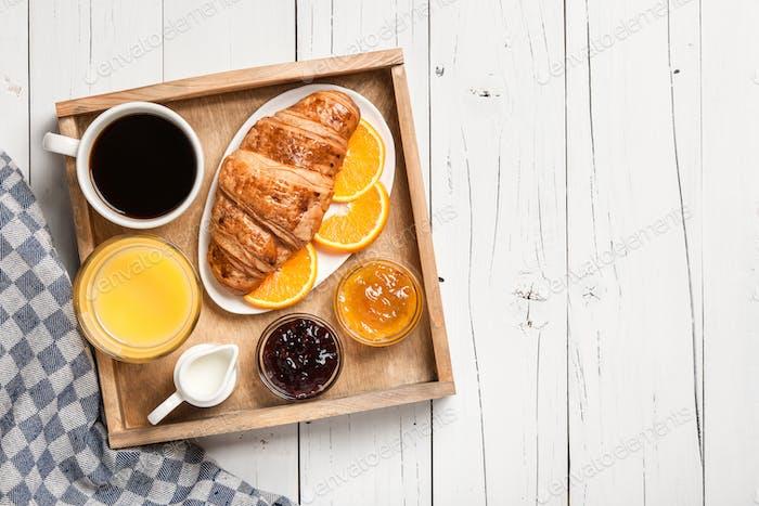 Breakfast with coffee, orange juice jam and fresh croissant