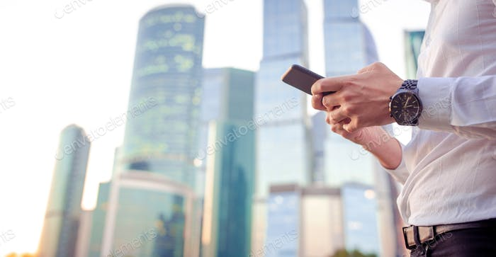Thumbnail for Closeup of male hands is holding cellphone outdoors on the street. Man using mobile smartphone