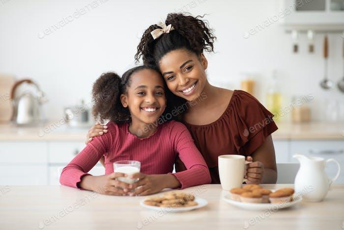 Loving black mother and daughter enjoying fresh cookies