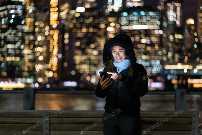 Asiatische Frau im Winteranzug mit Smart-Handy mit Smile-Action