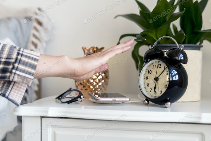 Woman reaching hand out to turn off the alarm