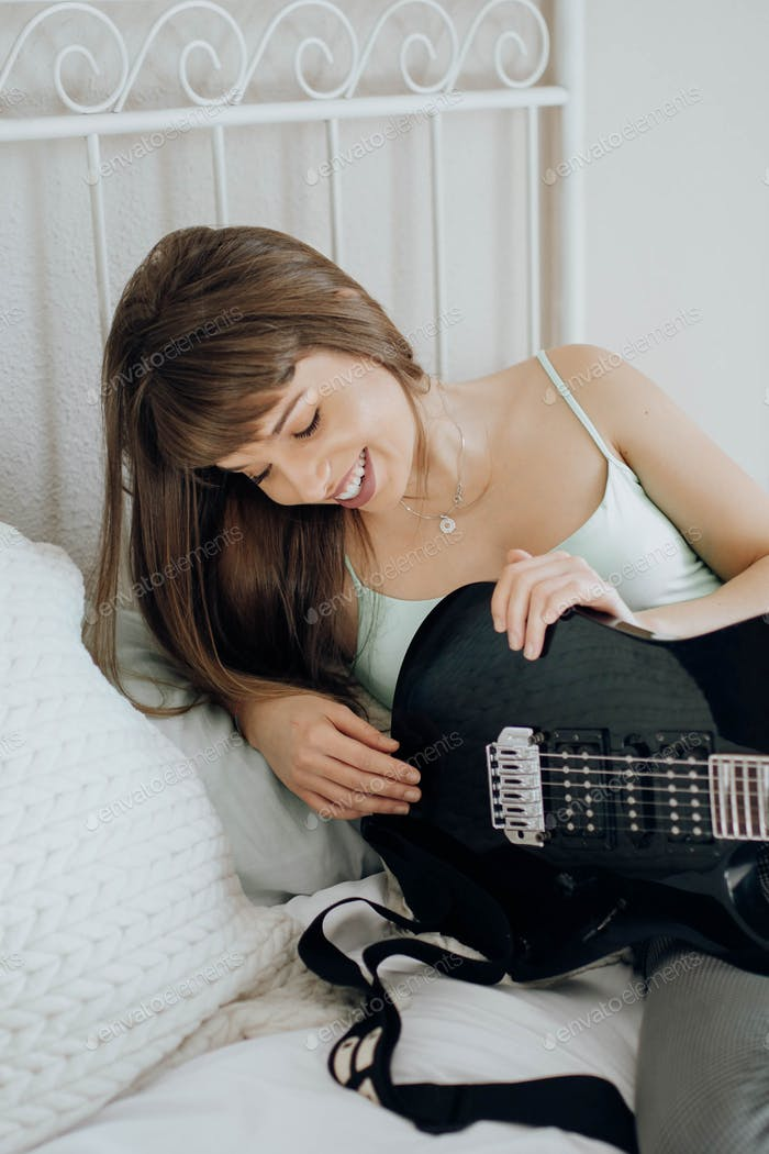 Young brunette woman playing guitar on bed