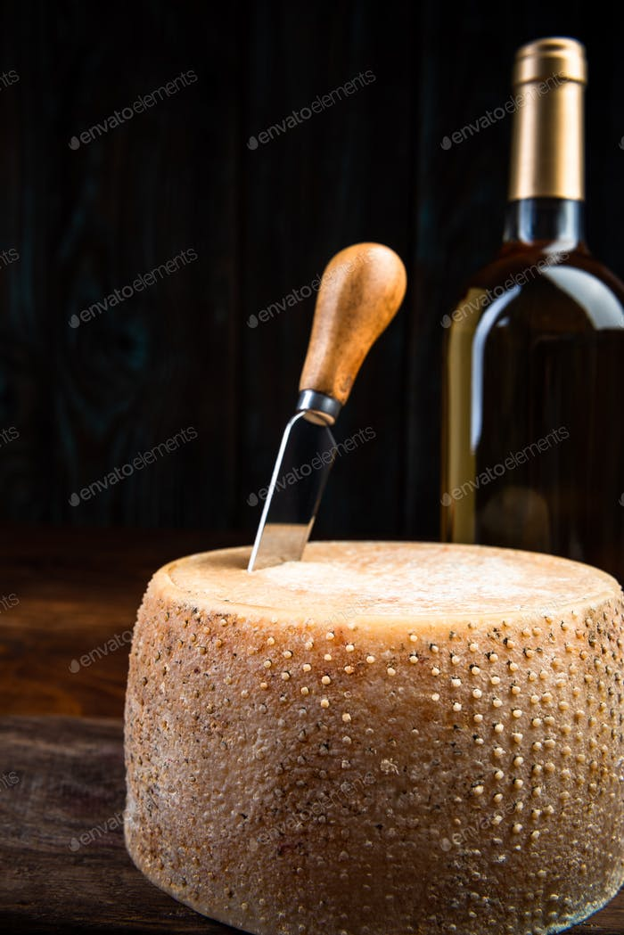 Hard Cheese Wheel Matured in Diary Cellar with White Wine Bottle