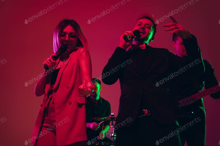 Young caucasian musicians, singers performing in neon light on red studio background