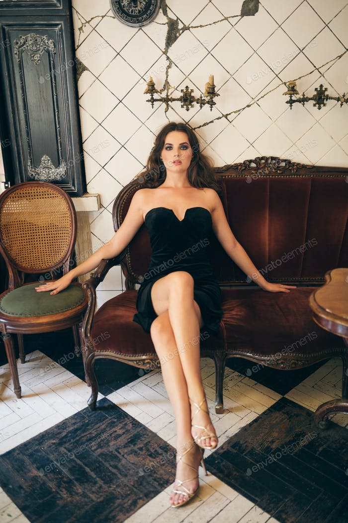 elegant beautiful woman sitting in vintage cafe in black velvet dress