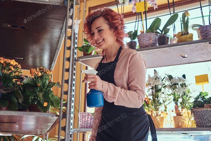 Hermosa pelirroja florista con uniforme de trabajo en una floristería.