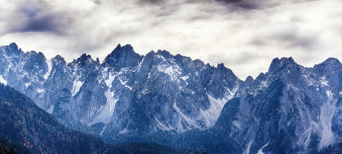 Panorama of Dachstein mountains peaks with sunset light Austria. Peaks covered with clouds
