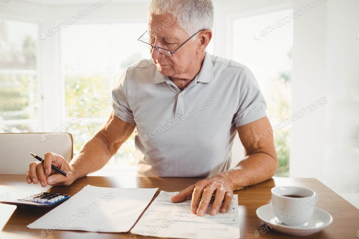 Worried senior man with tax documents at home