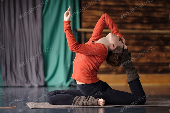 Young sporty woman practicing yoga, doing Eka Pada Rajakapotasana pose