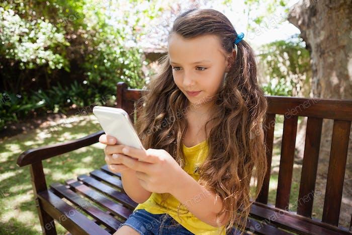 Mädchen mit Handy beim Sitzen auf Holzbank