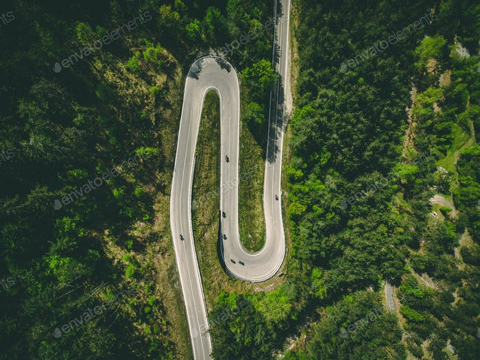 Aerial view of winding road with cars and motorcycles in Italy