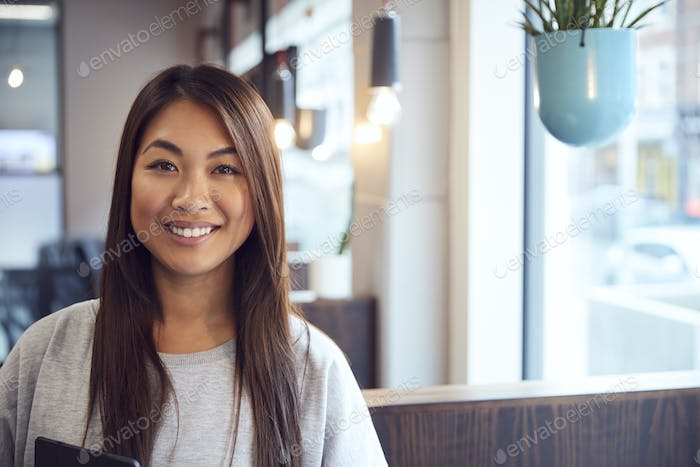 Head And Shoulders Portrait Of Smiling Young Asian Businesswoman  Working In Modern Office