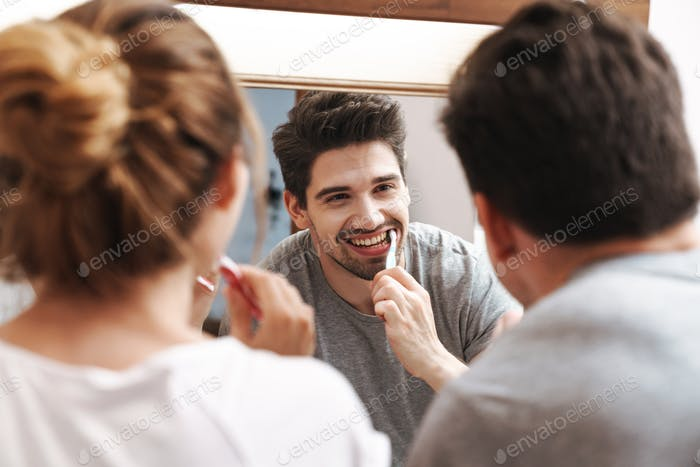 Image of cheerful couple cleaning teeth together in bathroom