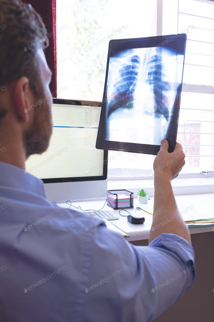 Rear view of male Caucasian doctor looking at x ray in clinic
