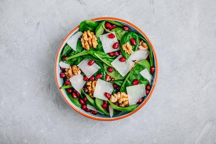 Spinat-Salatschüssel mit Granatapfelkernen, Walnüssen und Käsescheiben.