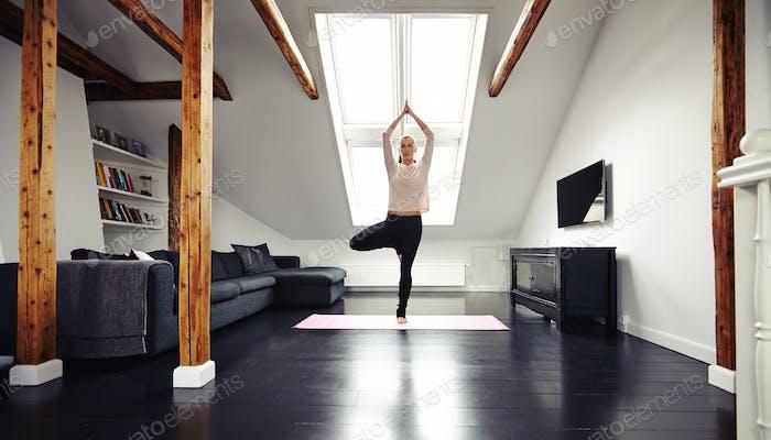 Junge Frau stehend in Yoga-Position