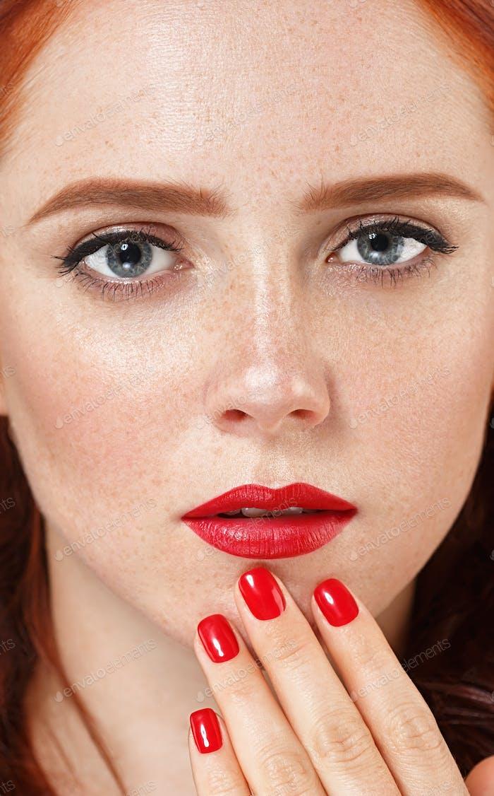 Schöne Frau Porträt mit Blume im Haar. Maniküre rote Lippen und Nägel weißen Hintergrund
