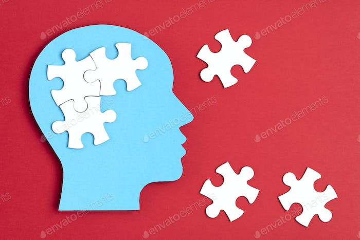 Papercut head with jigsaw puzzle pieces inside. Mental health problems, psychology, memory, logic