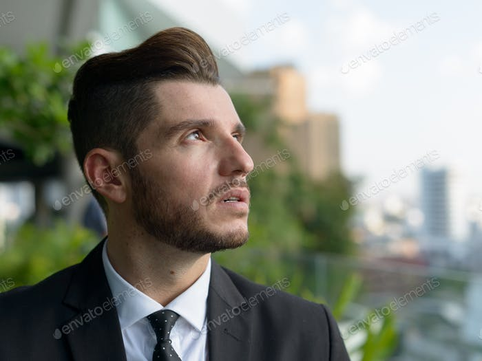 Handsome bearded Hispanic businessman with nature in the city outdoors