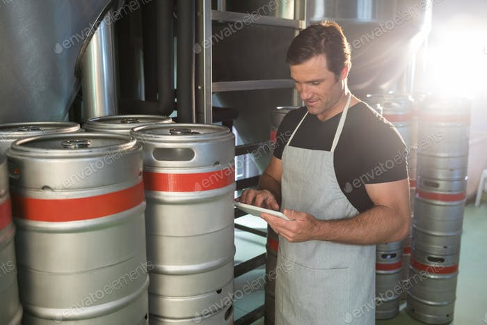 Worker using digital tablet on notepad while standing by kegs