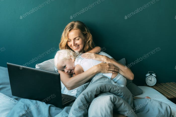 Happy family morning in bed. Mom hugs her little daughter. Remote work and family learning online.
