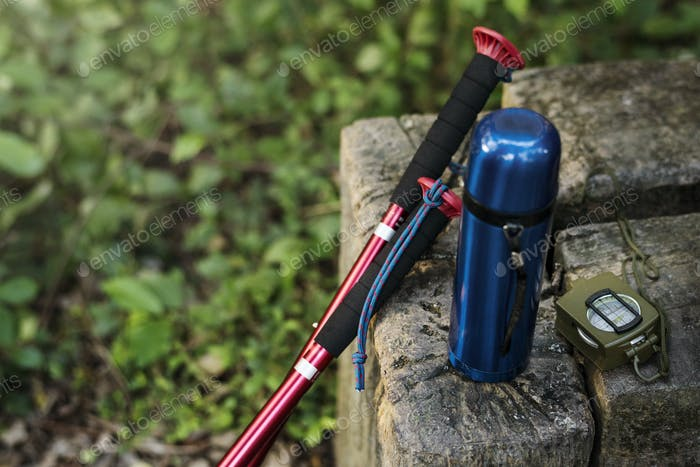 Trekking pole, water bottle and compass isolated on a rock outdoor